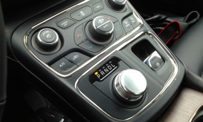The car's central controls include a dial gear shift which frees up space for storage and charging
